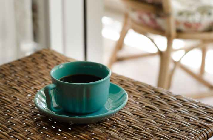 blue coffee cup with saucer filled with coffee on top of wicker table